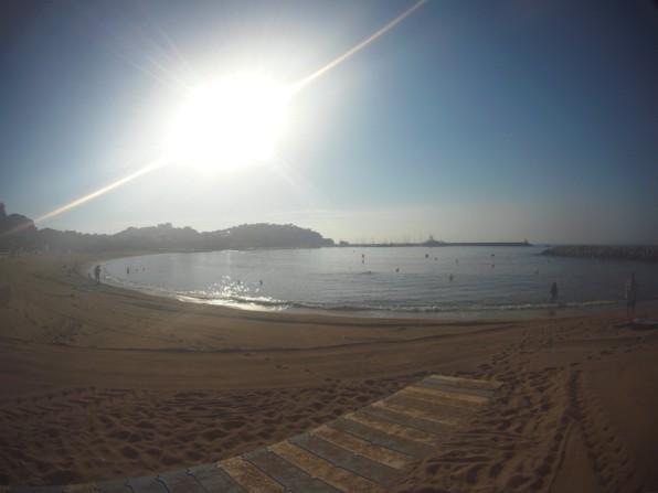 Vista de la playa, con el puerto al fondo