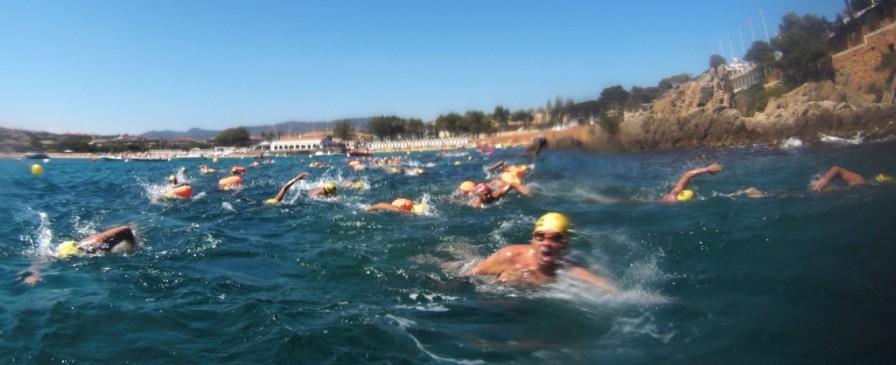 Al fondo, s'Agaró; hacia el frente, mucha gente nadando